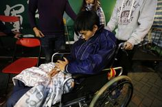Pro-democracy student leader Joshua Wong is pushed in a wheelchair into a makeshift shelter after...
