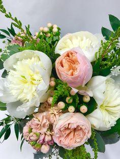 Peach and cream garden style bridal bouquet, featuring peach garden roses, cream peonies and peach hypericum berries.