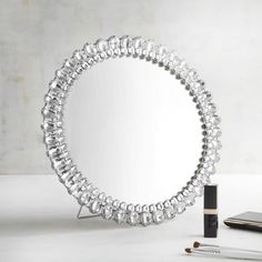 Make a sparkling statement with our silver jeweled accent mirror. It features large and small acrylic gemstones that frame a round mirror. It's versatile, too, with a removable easel that allows you to hang it on the wall. All we can say is, bling it on!