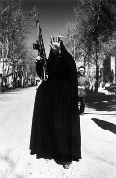 A woman, in black chador and carrying a G-3 machine gun, holds up her hand in a gesture of defiance to the camera, Tehran, 12th February 1979. She is amongst the revolutionary forces occupying Tehran University a day after the victory of Islamic Revolution in Iran led by Ayatollah Ruhollah Khomeini. (Photo by Kaveh Kazemi/Getty Images)