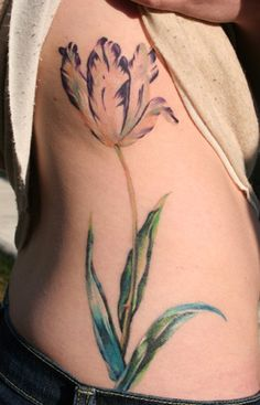 Single tulip plant Gorgeous tulip plant tattoo of a single flower and leaf that stretches from a girl's lower hip up to her ribcage. Big side purple tulip flower tattoo Tulips have pretty petals that are longer and peel out more than other flowers. This tulip was inked in a light peach, ...