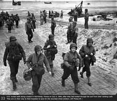 US nurses walk along a beach in Normandy, France on July 4, 1944, after they had waded through the surf from their landing craft. They are on their way to field hospitals to care for the wounded allied soldiers.