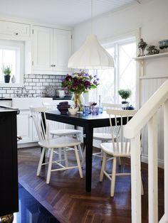 Lantligt kök med oljad ekparkett. Bord Allegro i svartbetsad massiv björk från Malmstensbutiken. Stolar Lilla Åland.