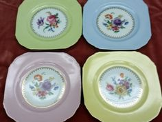 This foursome contains one plate each in light green, yellow, blue and pink. Each plate has a gold rim.