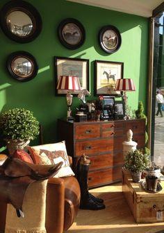 Темно-зеленые стены и темно-коричневый деревянный комод добавляет аристократизма в интерьер