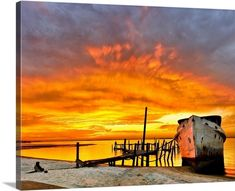 """Beautiful photograph of the sun rising off the Florida coast. """"Old Boat Yellow Red Sunrise"""" wall art by Eszra Tanner from Great BIG Canvas."""