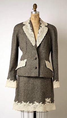 Ensemble  House of Dior  (French, founded 1947)    Designer:      John Galliano (British, born Gibraltar, 1960)  Date:      ca. 1996  Culture:      French  Medium:      (a–c) wool, cashmere, elastane  Dimensions:      Length at CB (a): 25 in. (63.5 cm) Length at CB (b): 30 in. (76.2 cm) Length at CB (c): 20 1/2 in. (52.1 cm)  Credit Line:      Gift of Mireille Levy - Lausanne, 2001  Accession Number:      2001.696.3a–c