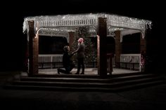 Outdoor winter engagement session with Christmas lights in the town square gazebo.  Romantic proposal idea! by Awakened Light Photography, Michigan wedding photographer