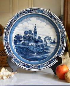The plate is entirely hand painted with original cobalt blue Delft pigments featuring a small Dutch village landscape with a tower, windmill, houses