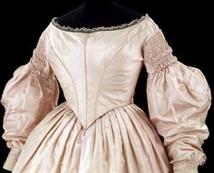 "Dress (detail): ca. 1838-1842, English, silk, trimmed with silk braid, lined with cotton, metal, boned; hand-sewn. ""This dress demonstrates the fashionable style of about 1840. The skirt of the dress is fuller than in the 1830s, and so heavy that it is made separately from the bodice. The bodice is pointed at the front of the waist and boned to hold the point in place. Full, 'bishop'-style sleeves are set below the shoulder and the bodice has a wide, off-the-shoulder neckline..."""