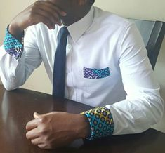 A regular blue shirt will do for the average guy, but for the trendsetter it needs to have beautiful accents. Classy blue shirt with Ankara (African Print) cuffs and accent on the the pocket. *The shirt comes with basic black and silver cufflinks. African Print Dress Designs, African Print Shirt, African Shirts, African Outfits, Ankara Designs, African Attire, Latest African Styles, Ankara Styles For Men, Latest Ankara
