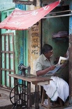 Waiting for a customer- but not whiling away time. Reads a newspaper!