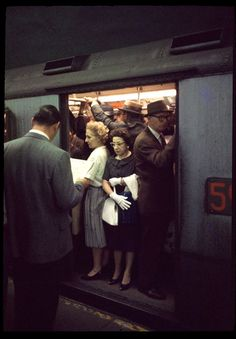 1950's New York City subway system at rush hour-straight out of Mad Men.  That's Don reading the newspaper with his back to the camera.
