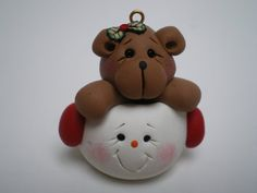 Polymer clay teddy bear Christmas ornament.  Teddy is popping his head out of a snowman head.  Red ear muffs on the snowman  Accents of holly