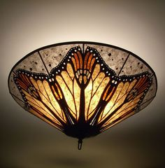 "This is such a beloved butterfly, recognizable by its delicately cut edge and its orange and black coloration. Mary Shilman's impressive 30"" mica ceiling light celebrates this Monarch of the butterfly world. Taking this wing and repeating it creates some unexpected and delightful natural shapes - whale fluke, flowers, stamen and pistils. It delights the eye."
