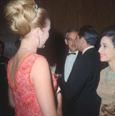Princess Grace Kelly in Givenchy coral dress and Prince Rainier of Monaco at Le Bal de Petits Lits Blancs held at Powerscourt in Enniskerry, County Wicklow, Ireland in July 1965. The coral dress was designed by Givenchy of Paris, executed by Marie Therese of Nice and is now a piece in the Drexel Historic Costume Collection in Philadelphia.