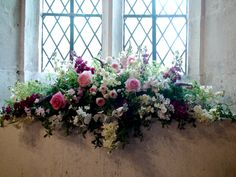A pretty arrangement for a church windowsill with roses, stocks and snapdragons, by Foxgloves & Roses.