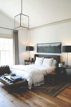 deep & rich tones/structure with bed, carpet, and accessories with airy bedding and a focal light fixture