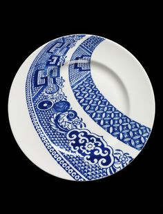 Plate, bone china, transfer-printed in enamel, 'Border', designed by Robert Dawson, made by Josiah Wedgwood & Sons, Stoke-on-Trent, 2005.  The Willow Pattern was first developed in England around 1800. It remains one of the most popular and immediately recognisable ceramic designs. Here, Robert Dawson takes elements from the iconic pattern – pagodas, Chinese figures crossing a bridge, two lovebirds – and uses digital technology to distort and make us look afresh at the familiar imagery.
