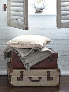 set of two trunks stacked on top each other with blankets thrown on top underneath a rustic window with shutters Vintage Suitcases, Vintage Luggage, Wellington House, Gladstone Bag, Cosy Sofa, Safari Chic, Vintage Trunks, Hat Boxes, Lounge Decor