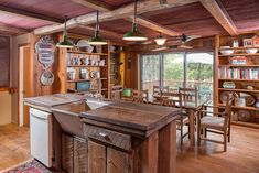 Rustic style kitchen with reclaimed wood counter island, wood floors and beam ceiling