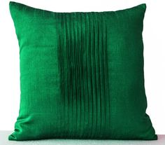 Throw pillows in emerald green dupioni art silk with pintucks in the middle to create a ripple effect. These precise waves of pintucking turn the textural interest of your room up a notch.   Details -