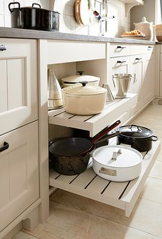 For easy access, store your pots and pans on open pull-out shelves underneath the hob | Canto Sand Grey Satin Schuller Kitchen | German Kitchens