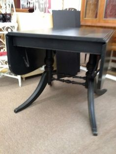 $259 - Large drop leaf table with two additional leaves has ornate base and metal cap feet - Painted black, distressed and wax finish. ***** In Booth D12 at Main Street Antique Mall 7260 E Main St (east of Power RD on MAIN STREET) Mesa Az 85207 **** Open 7 days a week 10:00AM-5:30PM **** Call for more information 480 924 1122 **** We Accept cash, debit, VISA, Mastercard, Discover or American Express