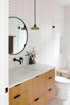 #Scandinavian #bathroom with subway tile and round vanity mirror