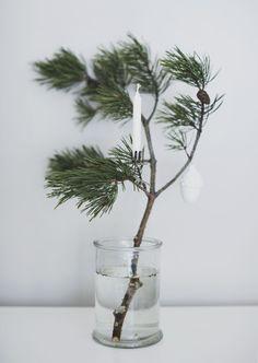 Une idée déco simple et facile à réaliser pour les fêtes avec une branche de sapin, un vase ou un pot en verre transparent rempli d'eau, une bougie et un objet déco blanc à suspendre. Bel effet ! #DIY #decoration #noel