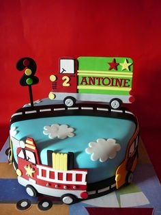 A trucks and car theme for Antoine, 2 years old. This is a marble cake with chocolate ganache covered with fondant. All the details are fondant. I had a lot of fun making this cute cake!