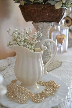 White flowers in a white pitcher always looks pretty and romantic.