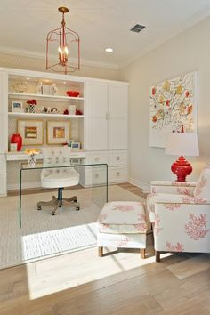 Pops of red keep this neutral contemporary home office far from ho-hum. A red wire chandelier quirkily lights the space with the help of a red table lamp. On the built-in shelf along the back wall, red accessories pick up the red flowers in the large artwork.