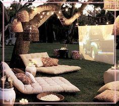 Tener un lugar como este en tu jardín no es nada costoso.   Composición a base de:  - Palet reciclados para base de los camastros.  - Lamparas de junco o lianas.  - Unos jarrones, almohadones y tu toque personal.  Woala!! recibe a tus invitados en una noche de verano y sorprendeles ;)  El mural que se ve es una pantalla de proyección, para que veas el cine al aire libre!!
