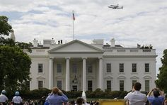 The space shuttle Discovery, riding atop a NASA 747 transport jet, does a final fly-by over the White House as tourists an Washingtonians watch and take pictures in Washington, April 17, 2012.