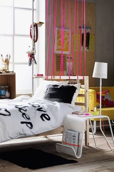 hot pink bungee cord creates the illusion of a room divider in a small space or studio.  2015 #IkeaCatalog #LiveBetterOrganized #apartmentjeaniePicks