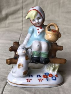 """This sweet figurine is in good, vintage condition. It has no chips or cracks. The bottom is stamped """"made in occupied Japan"""". There is a little blue paint on one knee. The figurine is 4.5"""" high, 3"""" long, and 1.75"""" wide. Please see my pictures and message me with any questions. 