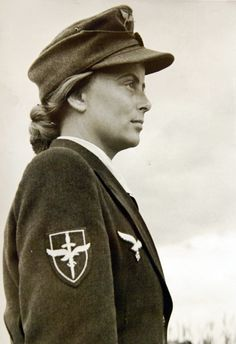 "German women ""Flakwaffenhelferinnen"" of the anti-aircraft gun auxiliary. A woman shows the insignia of the Flakwaffenhelferinnen Corps on her dress uniform. Courtesy of the Library of Congress."