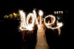 Bride and groom spell LOVE with sparklers at wedding reception by Outdoor Colorado wedding by Pippin's Pictures