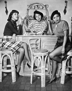 Three women enjoy their pool-side drinks and cigarettes, mid 20th century, LA