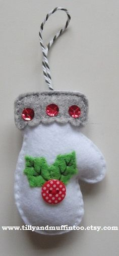 A handmade felt mitten with a holly design. This listing is for ONE decoration/ornament/bauble. Each mitten is has felt holly leaves, a polka dot button berry,and three red sequins on the cuff for added texture and detail. The mittens are stuffed with polyester filling that meets British & EU safety standards and they are finished with a bakers twine loop for hanging on the tree or other area. The mittens measure approximately 2.2 inches by 3.1 inches (5.5cm by 7.8cm) excluding the ribbon…