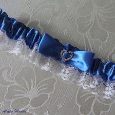 http://www.fler.cz/zbozi/podvazek-modry-se-srdickem-7010356 Krajkový svatební podvazek  z bílé krajky a středně modré ( Imperial Blue ) saténové stuhy , dozdobený mašličkou a štrasovým srdíčkem o velikosti 15 x 16 mm. Šíře podvazku je 4 cm