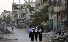 Palestinian girls walk past buildings which were destroyed by Israeli strikes on their way to school in the Shejaiya neighbourhood of Gaza City on September 14, 2014 (AFP Photo / Mahmud Hams)