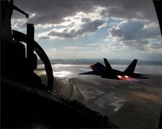 Military Aviation — fcba: An F-22 Raptor flies over the wet lakebed...