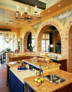 """Brick arches, a terracotta tile floor, warm color tones with bright color accents and painted murals all go into styling a """"Tuscan Kitchen."""" Rough wood beams and wrought iron lighting lend to the effect."""