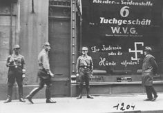 "Shortly after the German annexation of Austria, Nazi Storm Troopers stand guard outside a Jewish-owned business. Graffiti painted on the window states: ""You Jewish pig may your hands rot off!"" Vienna, Austria, March 1938."