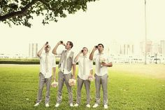 Groom and groomsmen drinking beer and holding bouques. Love this picture idea.