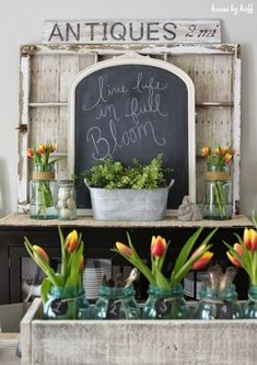 Buffet decorated with an old window backed with pallet wood, chalkboard, mason jar vases, galvanized container, etc.