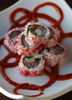 """""""Ring of Fire"""" (salmon, yellowtail, super white tuna, spinach, cilantro, jalapeno, habanero masago, sriracha sauce.)"""