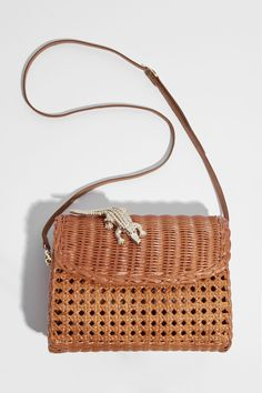 Handmade Shiny natural rotin bag.Stamped by a golden crocodile brass fixed to the flap.Removable leather strap of 59,5in, to wear across or on the shoulder.A small magnetic flap assure more security inside.Velvet fabric lining with a zipped pocket, sig...